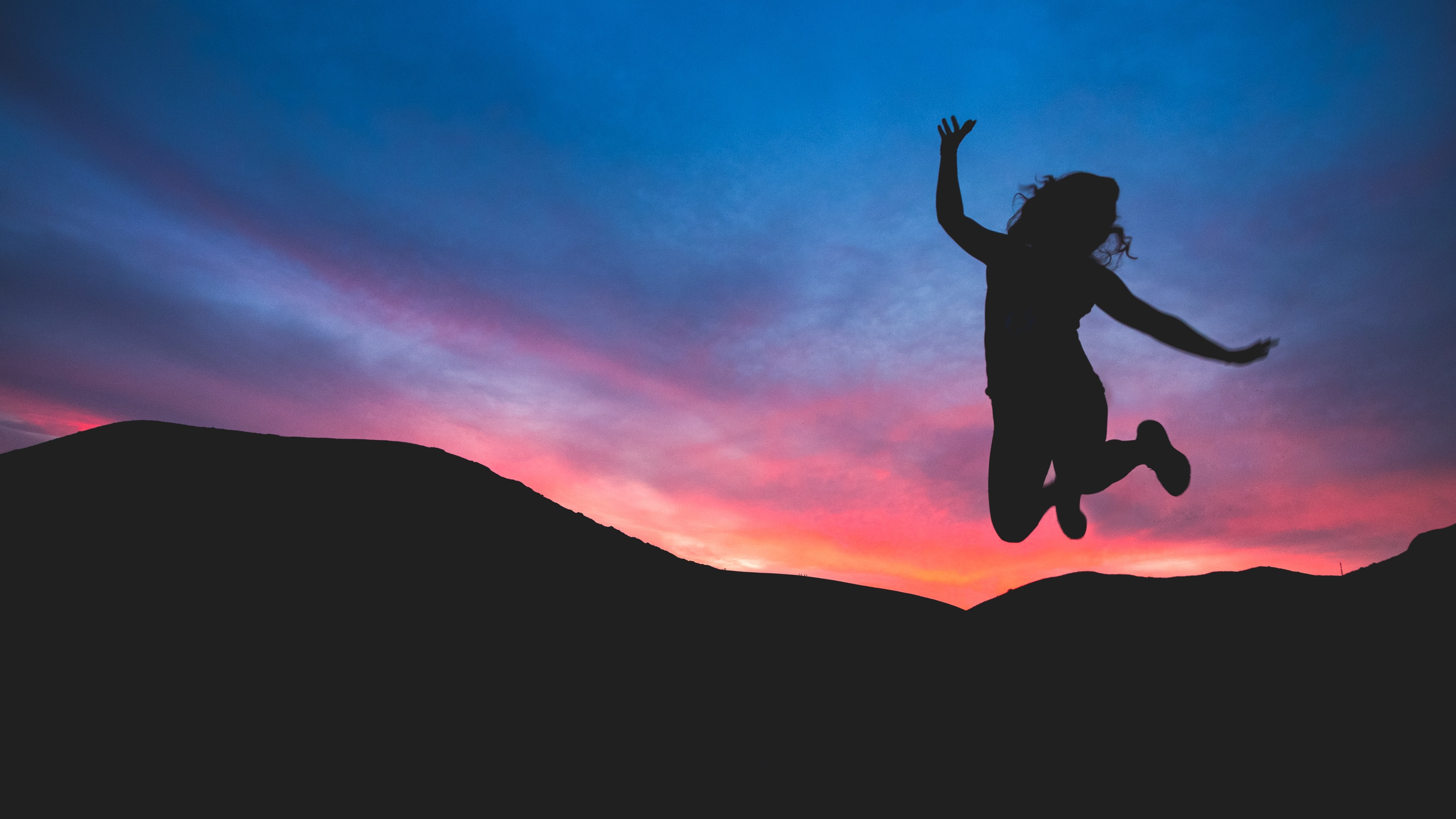 Silhouette girl jumping at sunset