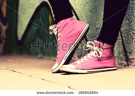 stock-photo-close-up-of-pink-sneakers-worn-by-a-teenager-grunge-graffiti-wall-concepts-of-teen-rebel-186952664
